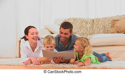 Family reading a book together on t
