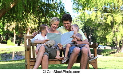 Family reading a book while sitting