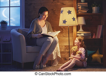 Family reading bedtime. Pretty young mother reading a book ...