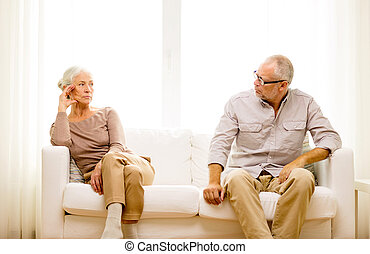 senior couple sitting on sofa at home - family, relations, ...