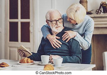 Positive joyful woman hugging her husband