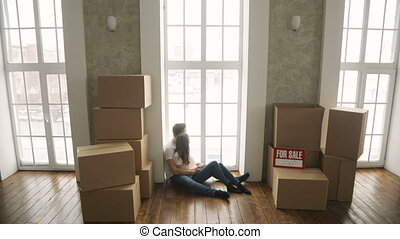 family relaxing and laughing after unpacking cartons from house move