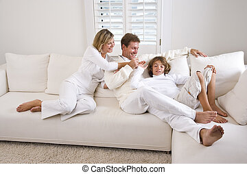 Family relaxing at home on white living room sofa