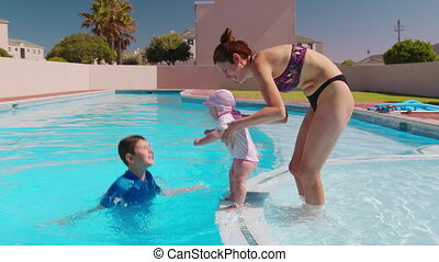 Family relaxing in outside swimming pool. Boy jumping into the pool and splashing water onto mom and little sister bathing. Summer fun.