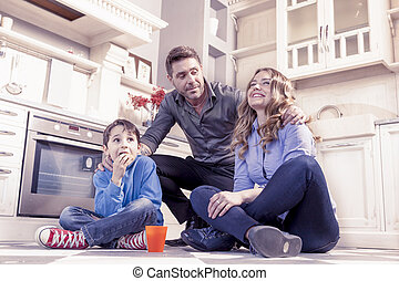 family relaxing on floor in the kitchen