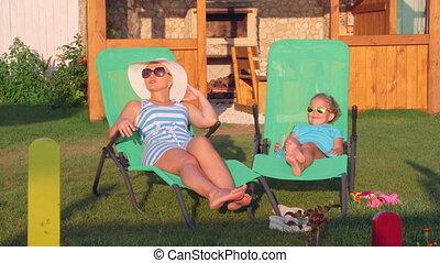 Family relaxing on patio loungers in backyard enjoying sunny...