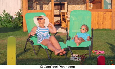 Family relaxing on patio loungers in backyard enjoying sunny summer day