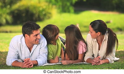 Parents chatting and their two children while lying on the grass