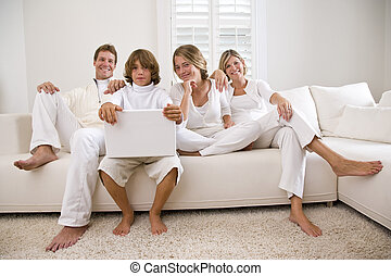 Family relaxing on white sofa with laptop