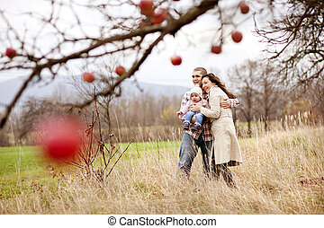 Happy and young family relaxing together in autum nature