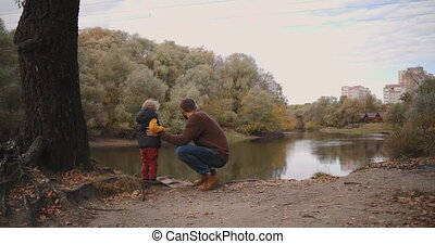 family rest in autumn forest, father is speaking to child son and showing picturesque lake in forest, hiking