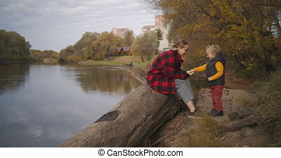 family rest in park at autumn day, young mother is playing with her little child on shore of river in forest