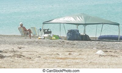 Family resting in a tent on the beach