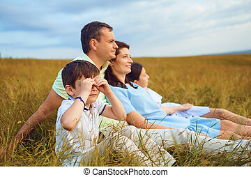 Family resting together sitting on grass in nature.