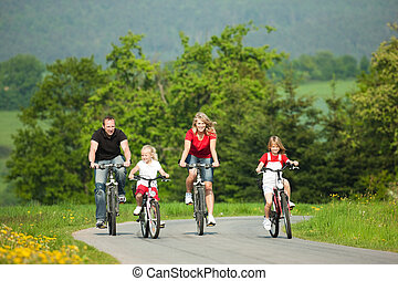 Family riding bicycles - Family with children having a ...
