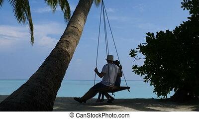 Family riding on a swing on a beautiful beach. Beautiful...