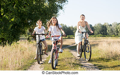 Family riding on bicycles in meadow at sunny day - Happy...