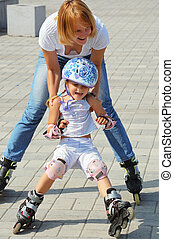 family rollerblading - daughter and mother having fun on...