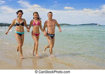 family running at the beach