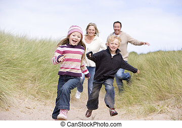 Family running on beach smiling