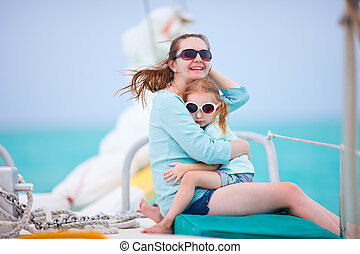 Mother and daughter relaxing while sailing on luxury yacht