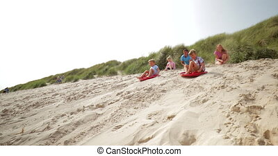 Family Sand Boarding Competitions - Slow motion shot of two...