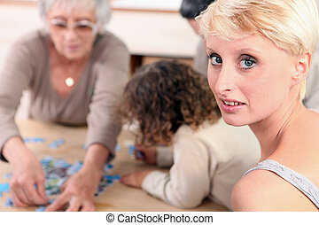 Family sat by table playing game