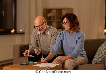 senior couple with bills counting money at home