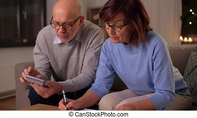 family, savings and people concept - smiling senior couple with papers and calculator at home