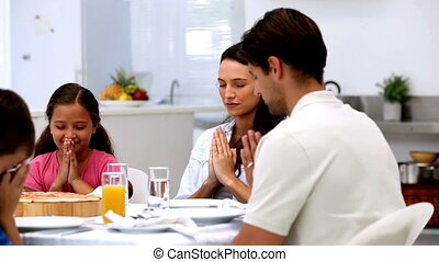 Family saying grace before dinner