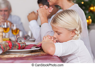 Family saying grace before dinner - Family saying grace...