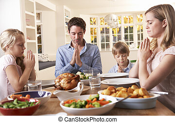Family Saying Prayer Before Eating Roast Dinner