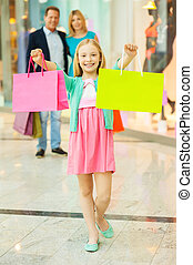 Family shopping. Cheerful family shopping in shopping mall while little girl showing her shopping bags and smiling