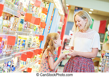 family shopping dairy food in grocery store or supermarket