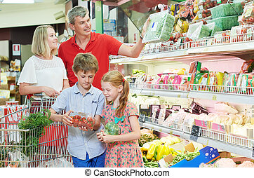 family shopping in grocery store or supermarket