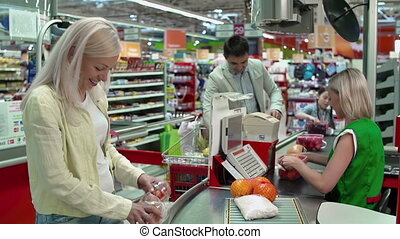 Pedestal down of family at cash-till buying food