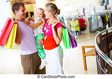 Family shopping - Portrait of happy couple looking at their...