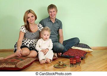 family sit on floor on pillow
