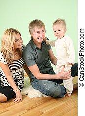 family sit on fur carpet