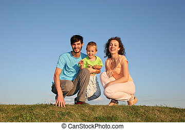 family sit on meadow