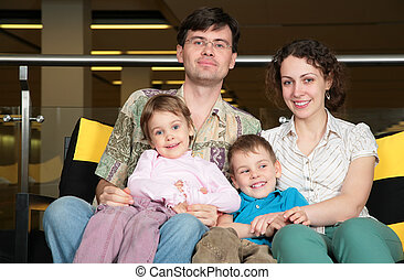 family sit on sofa in dark hall