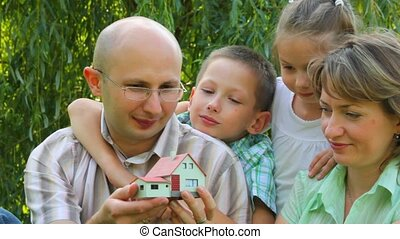 family sits in park and taking good look at toy house