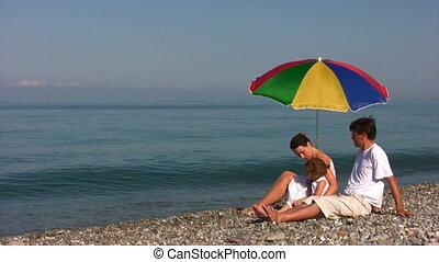 family sits near beach umbrella