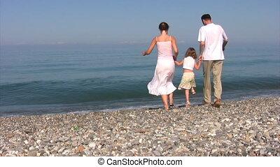 family sits on beach near sea surf