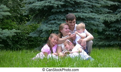 family sits on green grass against conifers