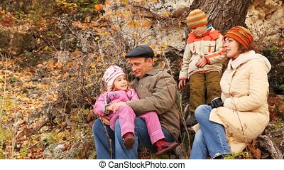 family sits on nature against trees and rocks