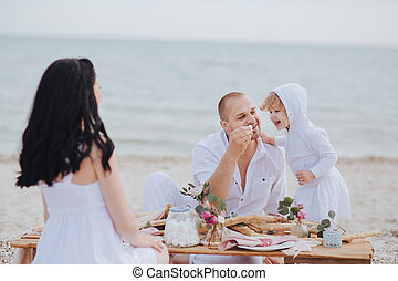 Family sitting at a table near the sea