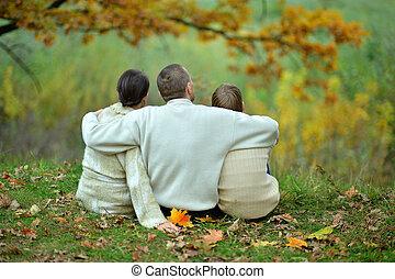 Family sitting in autumn park