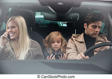 Family sitting in car - Photo of concentrated young man...