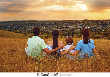 Family sitting in nature looking at beautiful sunset.
